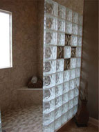 custom tile shower in columbus with a corner bench seat and glass block wall