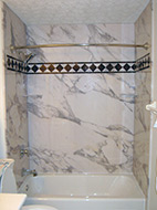 Calcutta gold bathtub wall surround and an acrylic tub with a tile accent border