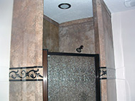 mocha travertine moldings around a shower enclosure with a framed door