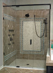 frameless pivoting shower door with a handheld shower and rain head