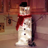 glass block snowman on a kitchen counter with lights