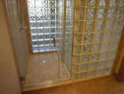 glass block shower walls and a frameless glass door