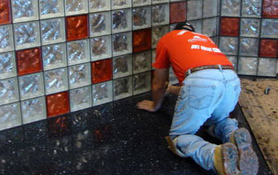 black grout being applied to a glass block counter wall