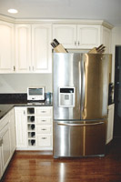 White contemporary kitchen cabinets with a stainless steel refrigerator cleveland