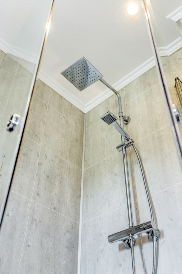 Decorative laminated wall panels in a rental home shower | Innovate Building Solutions | Innovate Building Solutions Multi Unit | #LaminateWallPanels #ShowerPanels #GroutFreePanels