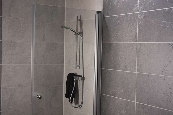 3D textured slate laminate grout free shower and bathroom wall panels | Innovate Building Solutions | Multi Unit | Luxury Apartments | #BathroomRemodel #ApartmentBathrooms #LuxuryBathrooms