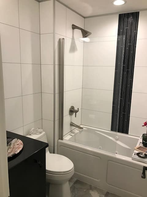 White high gloss laminate shower wall panels 24 x 12 with a decorative black accent trim in a Parma Ohio bath remodeling The Bath Doctor